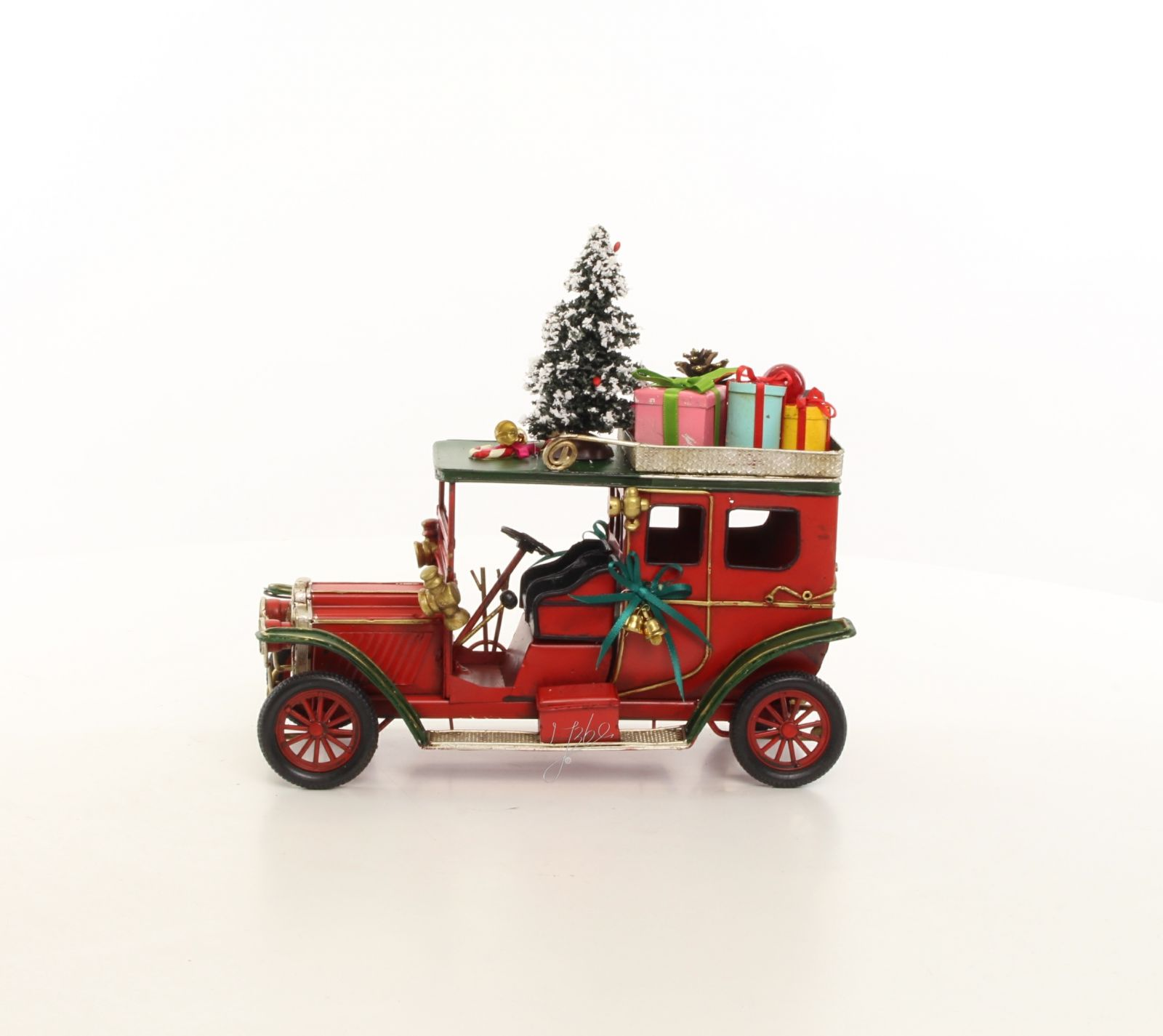 A TIN MODEL OF AN OLDTIMER CAR IN CHRISTMAS STYLE