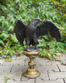 A large bronze eagle statue on a pedestal BrokInCZ