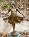 Statue of a cute girl in dress made of bronze