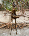 Statue of a woman on chair made of bronze