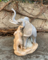 a Statue of an elephant with a child made of porcelain